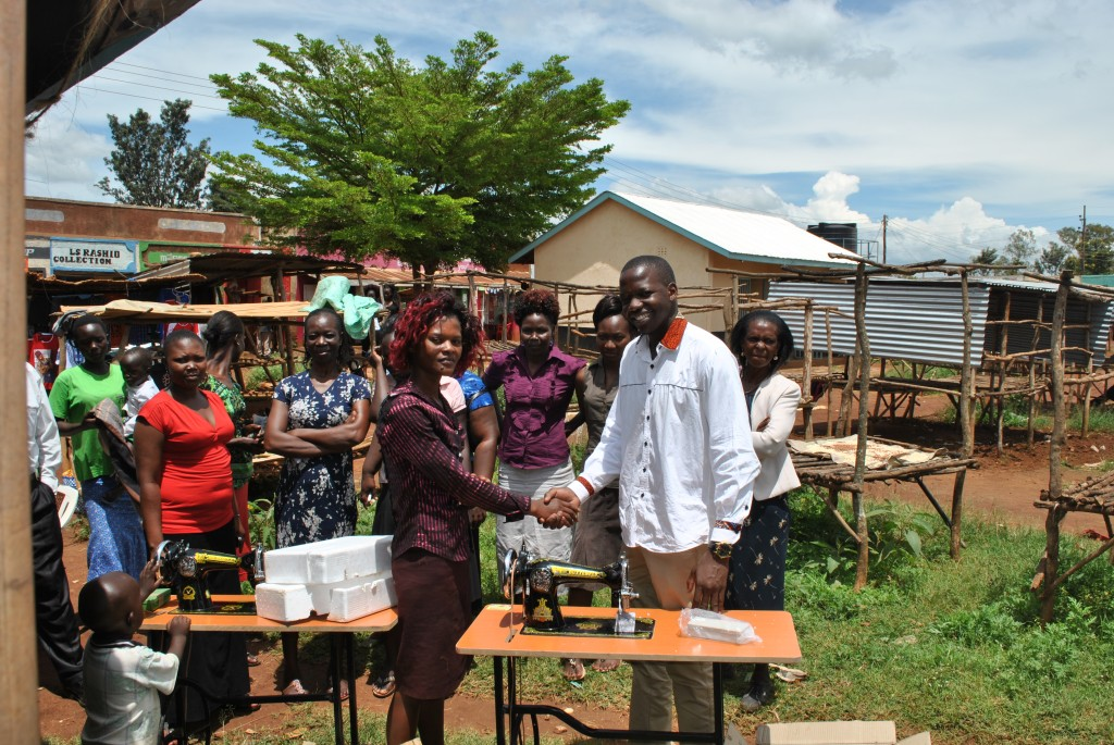 wesley-owiti-2-issuing-a-sewing-machine-to-a-beneficiary-in-ndori-market-siaya-county